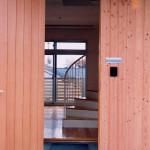 住戸B玄関。木の外壁に木の玄関扉